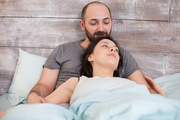 Relaxed young caucasian couple in the morning wearing pajamas.