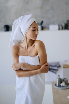 Relaxed young caucasian female model in white towel