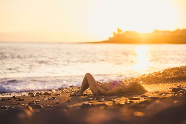 リラックスした若い白人女性は、ビーチの海の波の近くの海岸に横になりました。仕事と都市のライフスタイルからの休暇と旅行の概念のための夏の日没時間。黄金色と日光が戻ってきた