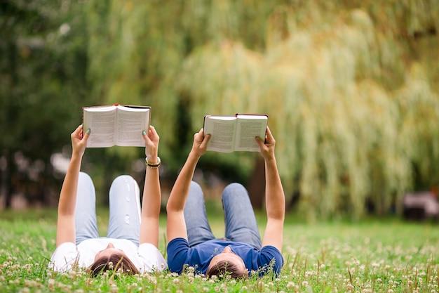 草の上に横たわっている間本を読んでリラックスした若いカップル