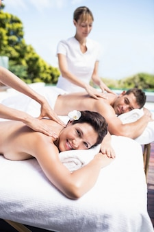 Relaxed young couple receiving a back massage from masseur in a spa