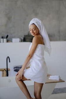 Relaxed young female model in white towel, feels refreshed after taking shower