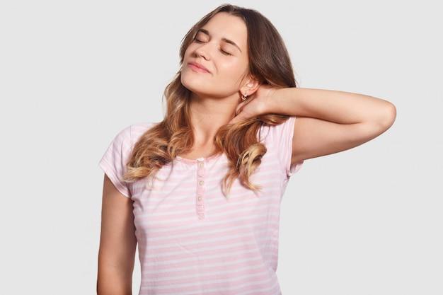 La giovane femmina rilassata allunga il collo dopo una lunga sdraiata a letto, ha un'espressione compiaciuta, tiene gli occhi chiusi, vestita in indumenti da notte, isolata su bianco. concetto di sonno e riposo