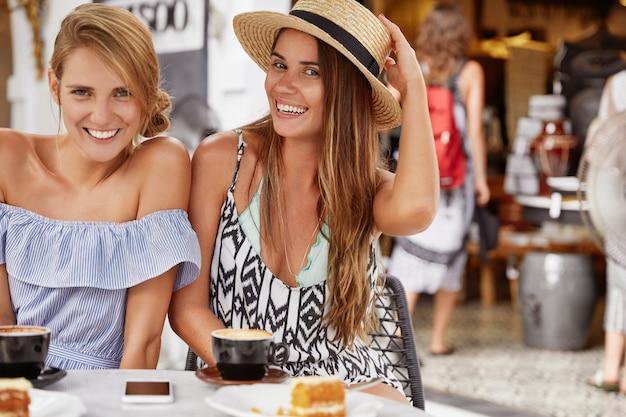 Giovani turiste rilassate si divertono insieme alla mensa, si siedono una accanto all'altra, indossano abiti estivi, circondate da caffè e gustosi dessert, hanno espressioni felici. concetto di amicizia