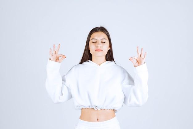Modello di ragazza rilassata che mostra le dita incrociate con gli occhi chiusi. Foto Gratuite