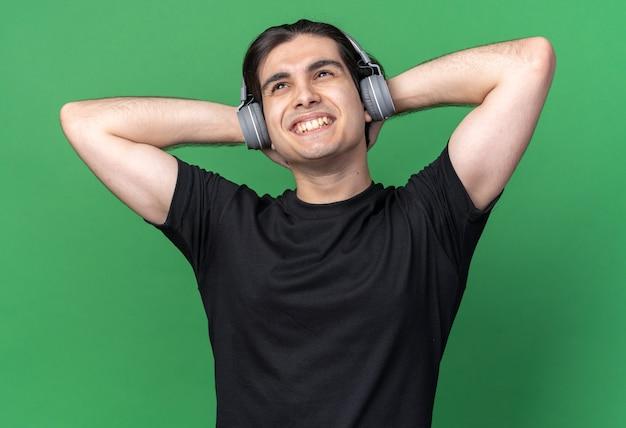 녹색 벽에 고립 된 목에 손을 잡고 검은 티셔츠와 헤드폰을 입고 편안한 젊은 잘 생긴 남자
