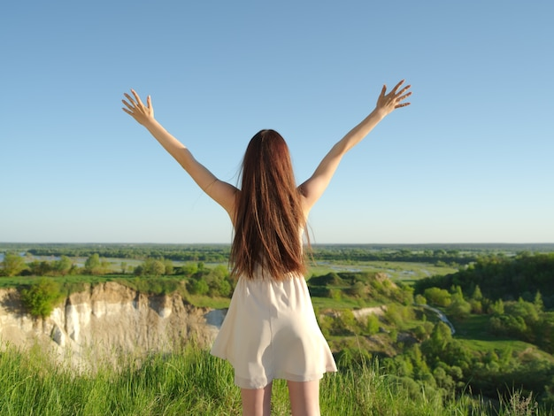 Relaxed young happy woman with raised arms outdoors in nature. young girl stands with her arms raised up to the sky.  peaceful girl standing by a cliff enjoying summer. - outdoors