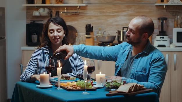 편안한 젊은 남편이 아내와 이야기하고 안경에 적포도주를 붓습니다. 촛불, 사랑, 기념일에 결혼을 축하하는 부엌 테이블에 앉아 있는 로맨틱한 백인 행복한 커플