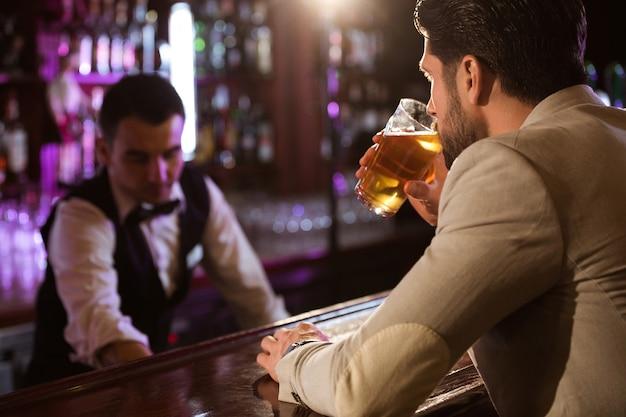 맥주 잔을 마시는 편안한 젊은 남자