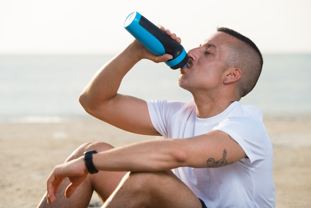 Relaxed young man drinking water from bottle