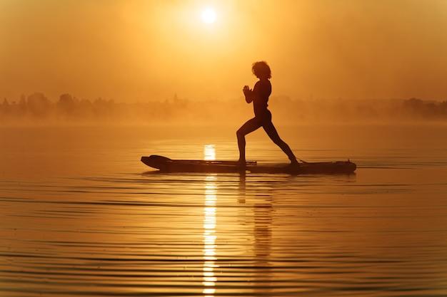 Расслабленный молодой человек в силуэте, сохраняющий баланс на доске sup на поверхности воды.
