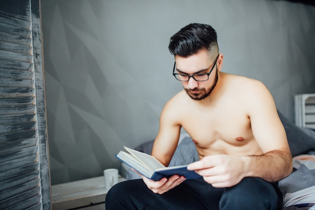 Relaxed young man reading an interesting book while lying in bed at home