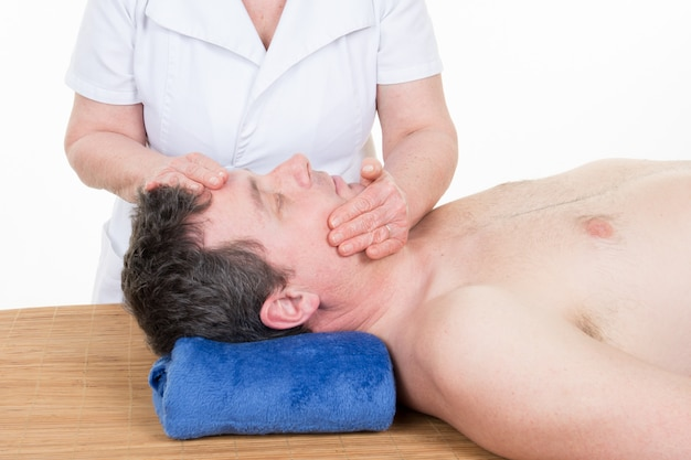 Relaxed young man receiving face massage treatment in spa