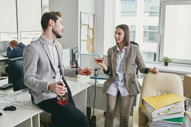 Relaxed young office colleagues leaning on tables and drinking whisky in modern office