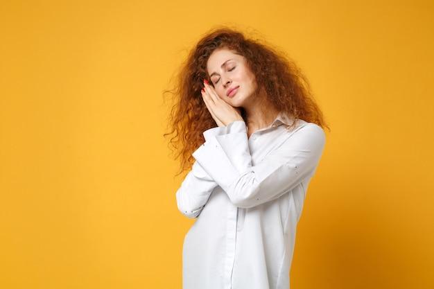 노란색 오렌지 벽에 고립 된 캐주얼 흰색 셔츠 포즈에서 편안한 젊은 빨간 머리 여자 소녀