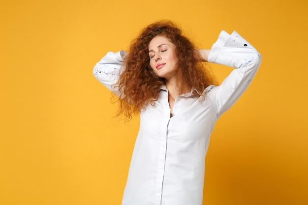 Расслабленная молодая рыжая девушка в повседневной белой рубашке позирует изолированной на желто-оранжевой стене