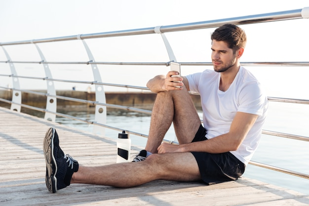 Relaxed young sportsman resting and using mobile phone sitting on wooden terrace