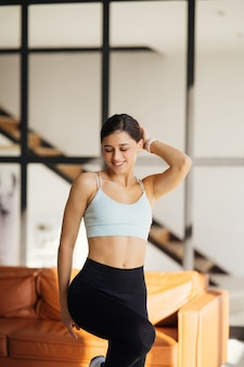 Relaxed young sportswoman dressed in activewear posing