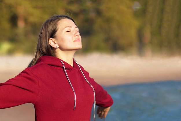 Relaxed young woman breathes fresh air in nature on the beach