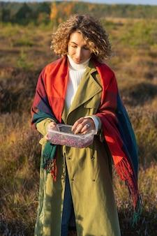 가을 햇살과 따뜻한 날씨를 즐기는 익은 크랜베리가 든 상자를 들고 있는 편안한 젊은 여성
