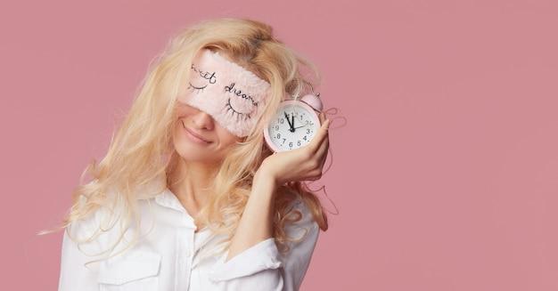 Расслабленная молодая женщина в пижамах и масках сна на розовой стене. будильник разбудил девушку