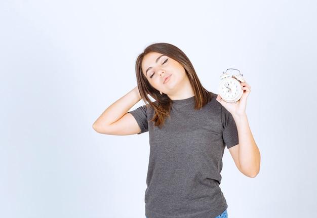 目覚まし時計を保持しているパジャマでリラックスした若い女性。