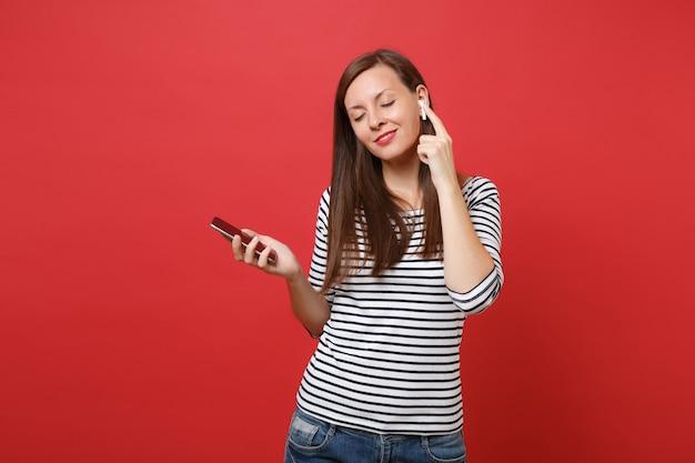 Расслабленная молодая женщина в полосатой одежде с беспроводными наушниками держит мобильный телефон, слушая музыку, изолированную на ярко-красном фоне. люди искренние эмоции, концепция образа жизни. копируйте пространство для копирования.