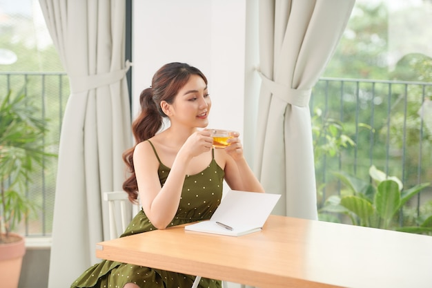 Relaxed young woman near big window at home