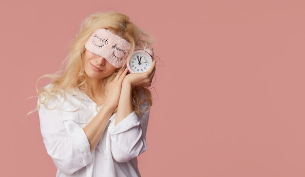 Relaxed young woman in pajamas and sleep masks on a pink wall. alarm clock woke up the girl