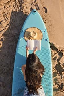 Расслабленная молодая женщина, читающая книгу на пляже