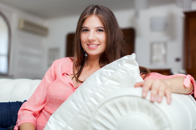 Relaxed young woman sitting on couch