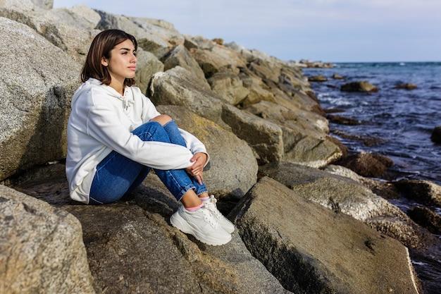Расслабленная молодая женщина, сидящая на набережной в солнечный день