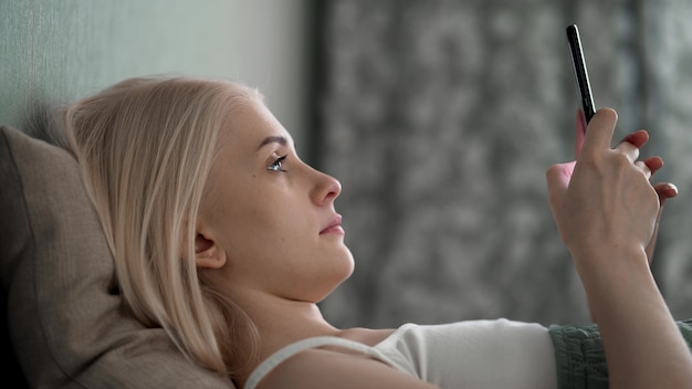 Расслабленная молодая женщина, использующая смартфон, просматривает социальные сети, проверяет новости, играет в мобильные игры или отправляет текстовые сообщения, сидя на диване. миллениальная женщина проводит время дома с мобильными гаджетами.