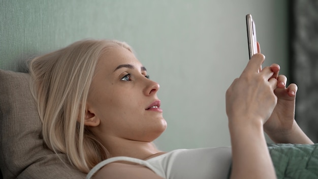 Relaxed young woman using smart phone surfing social media, checking news, playing mobile games or texting messages sitting on sofa.