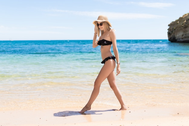 Relaxed young woman walking in bikini enjoying tropical beach summer vacation.