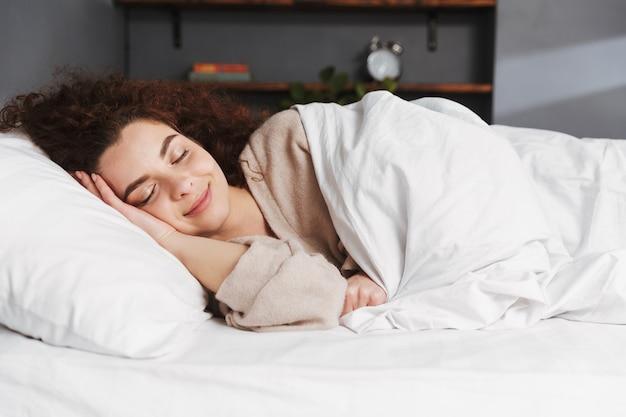 집에서 흰색 침대 시트에 침대에서 자고 집 옷을 입고 편안한 젊은 여자