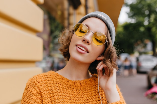 Giovane donna rilassata con pelle pallida che gode della musica con gli occhi chiusi in piedi sullo sfondo della strada
