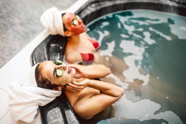 편안한 젊은 여성들은 수압 마사지 욕조에서 스파 절차를받습니다. 그들은 눈 위에 얼굴 마스크와 오이 조각이 있습니다. 모델은 편하고보기 좋게 보입니다.