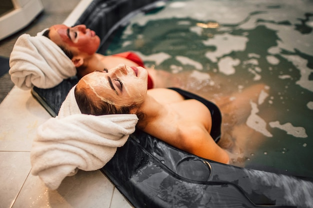 Relaxed young women sit in hydromassage bath. they have spa procedures. calm models wear swimwuits. they sleep. european model sit in front.