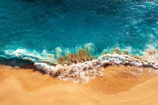 リラックスした空中ビーチシーン、夏休み休暇テンプレートバナー。波は驚くべき青い海のラグーン、海岸、海岸線でサーフィンします。完璧な空中ドローンの上面図。静かで明るいビーチ、海辺