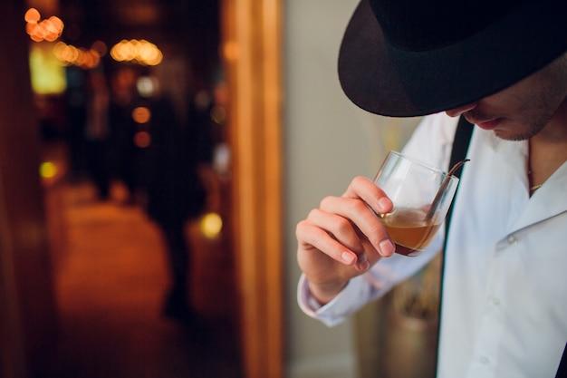 Отдых после тяжелого рабочего дня. уверенный зрелый бизнесмен сидит в баре и пьет виски