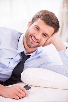하루 일과 후 휴식. 셔츠와 넥타이 침대에 누워 웃 고 잘생긴 젊은 남자