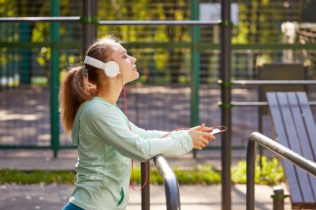 Отдых после фитнеса. молодая женщина слушая к музыке после тренировки outdoors. фитнес, спорт, концепция образа жизни
