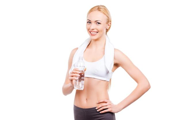 ジムで一生懸命働いた後はリラックス。水のボトルを保持し、白い背景に立って笑っている美しい成熟した女性