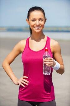 ジョギング後にリラックス。水でボトルを保持し、屋外に立って笑っている美しい若い女性