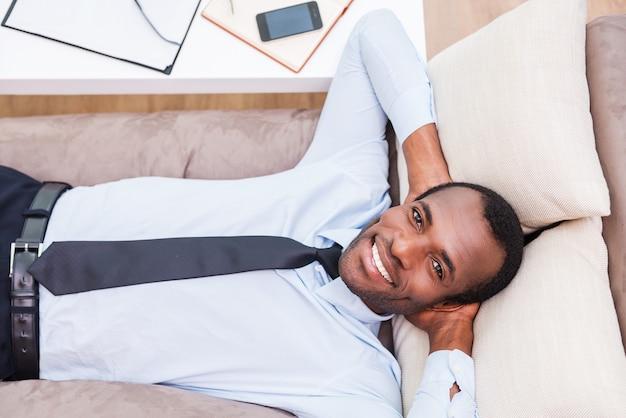긴 하루 일과 후 휴식. 셔츠와 넥타이에 잘 생긴 젊은 아프리카 남자의 상위 뷰