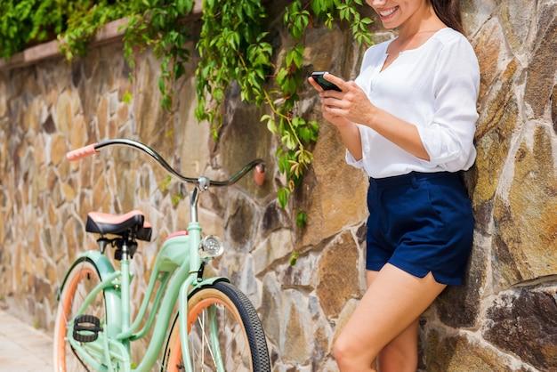 Расслабление после долгой езды. красивая молодая женщина держит мобильный телефон и улыбается, стоя возле своего старинного велосипеда