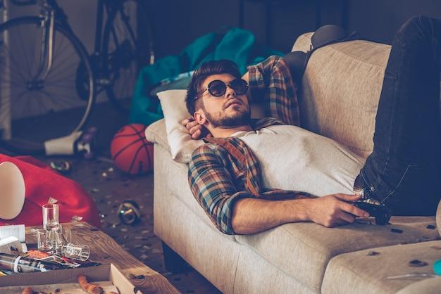 Расслабление после вечеринки. молодой красавец в солнцезащитных очках, лежа на диване
