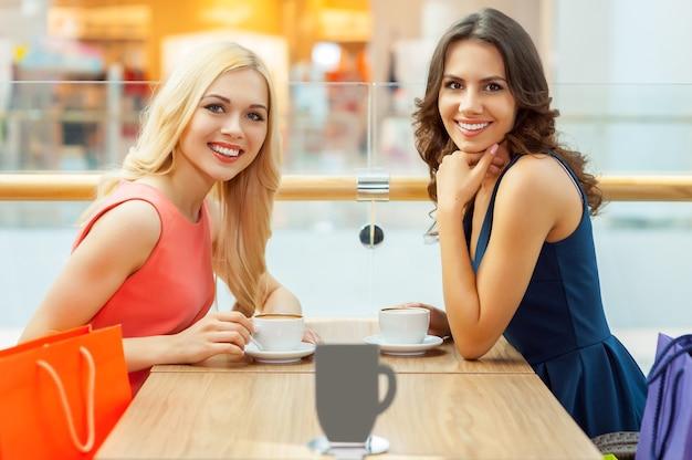 Расслабляйтесь после покупок. две красивые молодые женщины пьют кофе в ресторане и смотрят в камеру