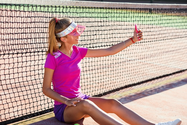 Relaxing after tennis training and using smart phone. young beautiful girl in pink uniform and sporty cap sits on a tennis court near the net and making selfie photo on smart phone at sunset.